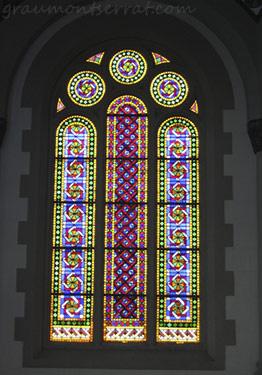 Vista en detall del conjunt d'un vitrall en arc de mig punt des de l'interior